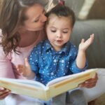 woman kissing a small child while reading a book